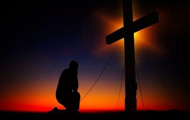 man kneeling cross
